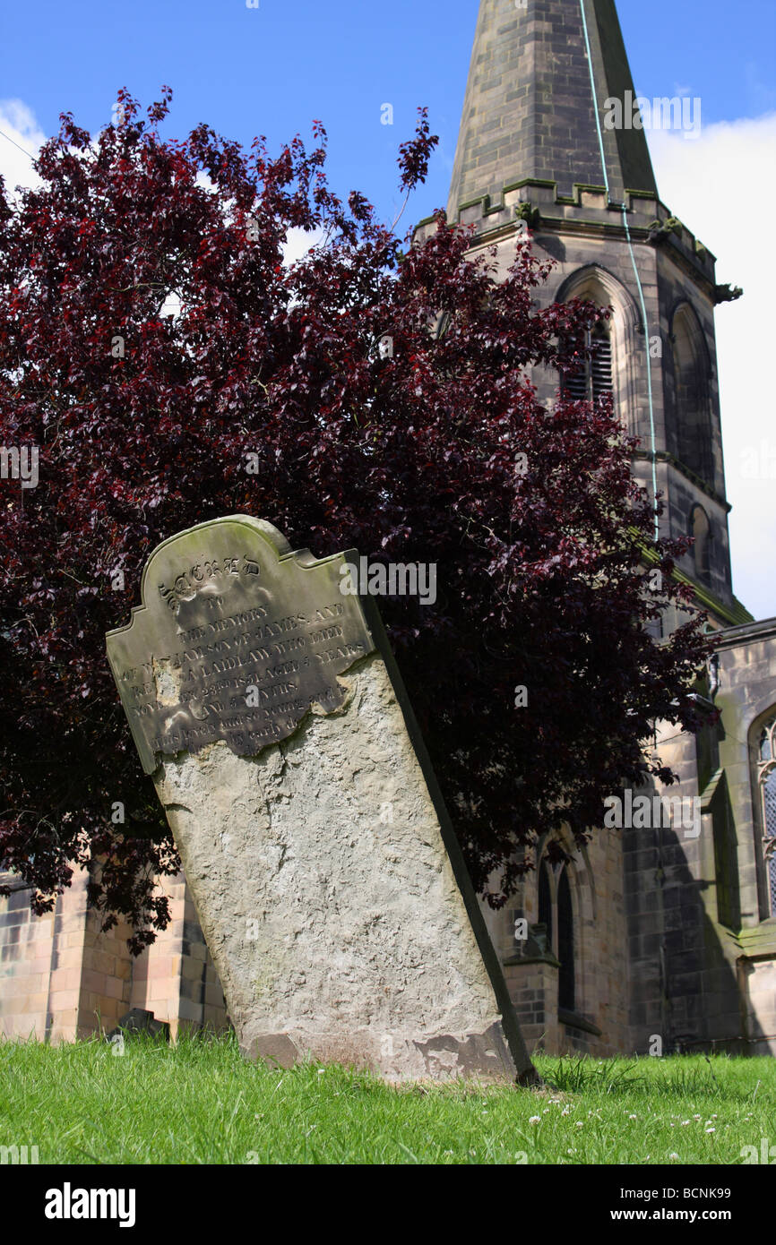An unsafe headstone in a churchyard. - Stock Image