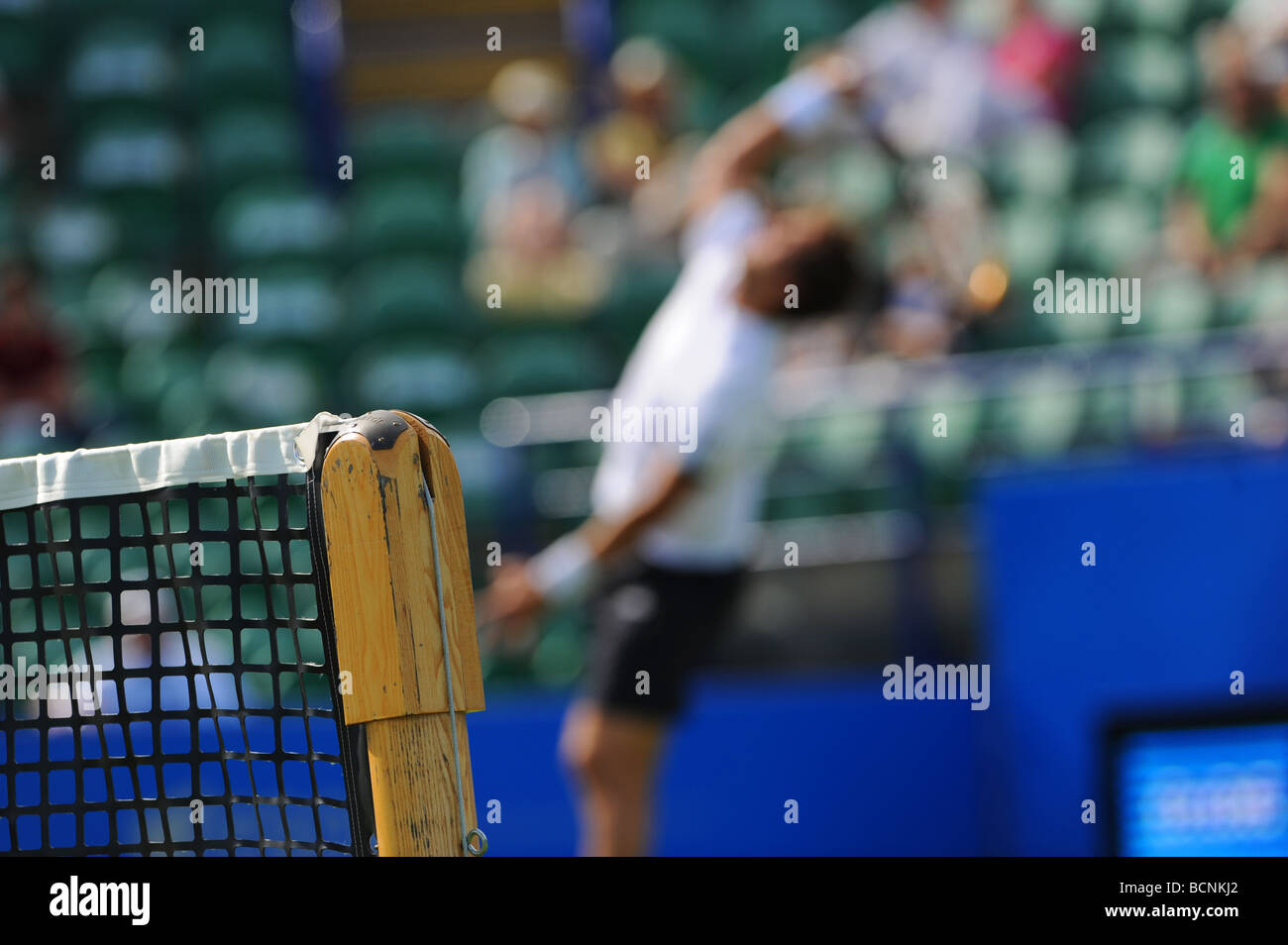 Out of focus tennis player serves - Stock Image