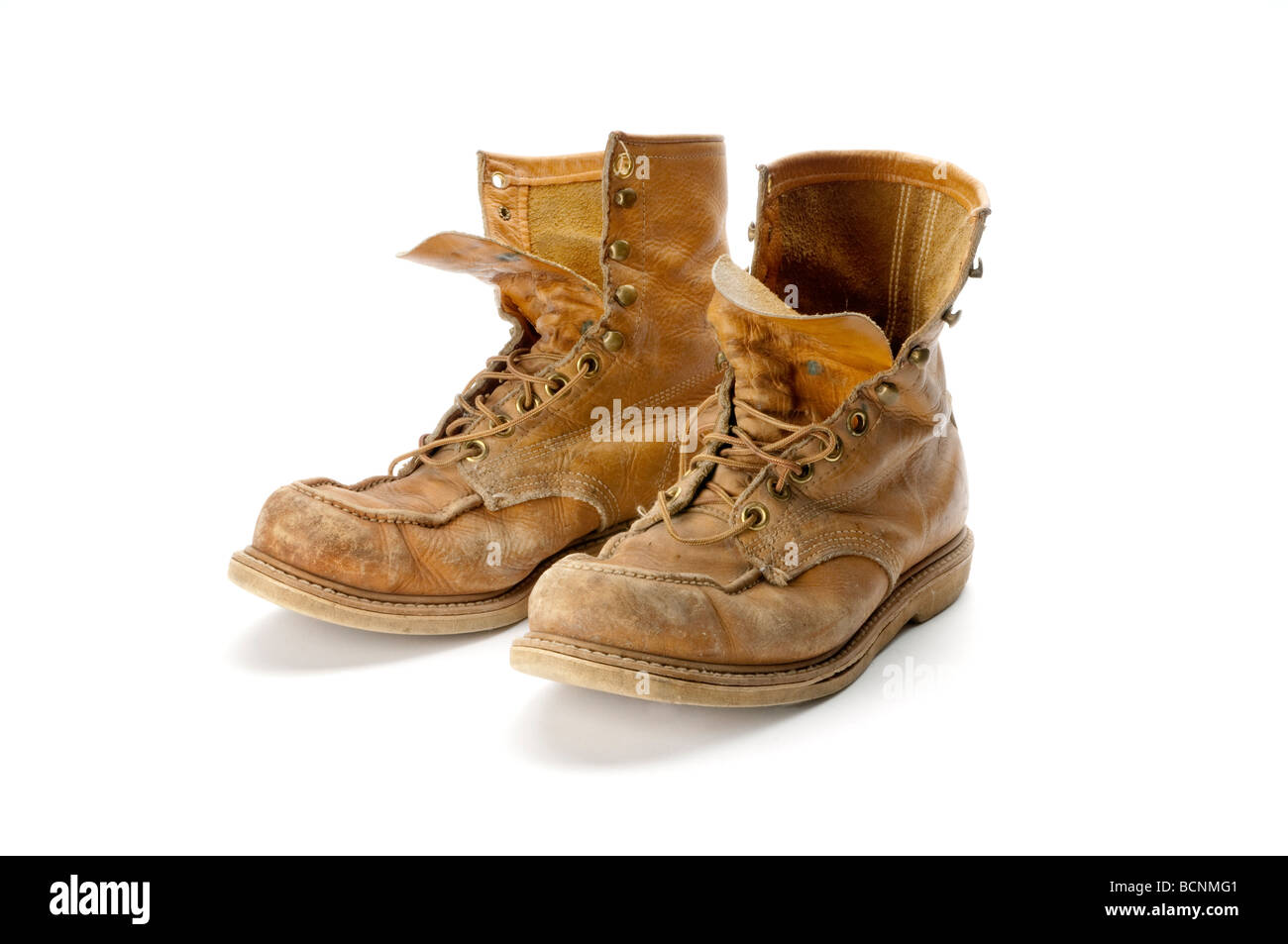 old pair of work boots on white background - Stock Image