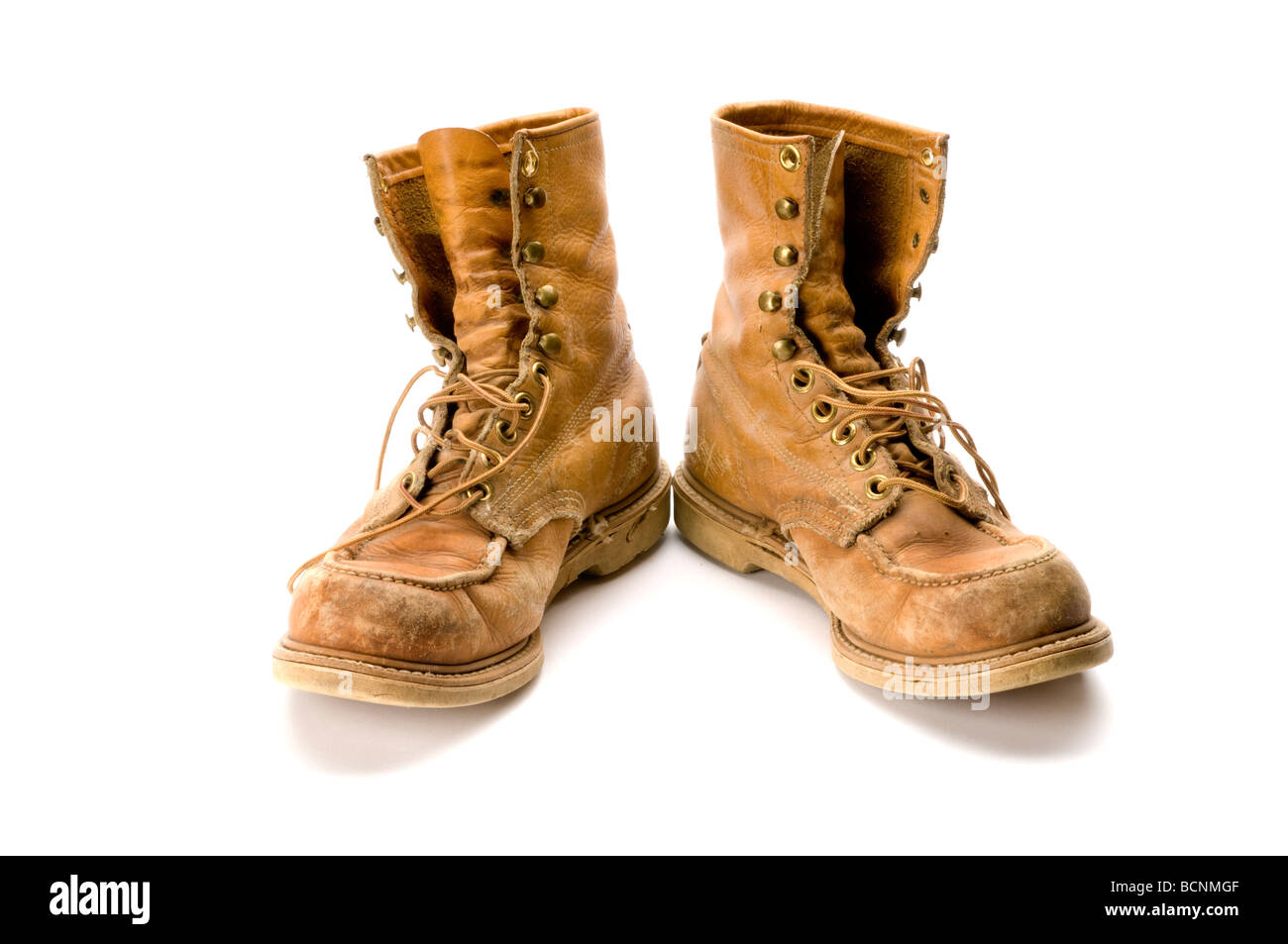 Old steel toed work boots on white background - Stock Image