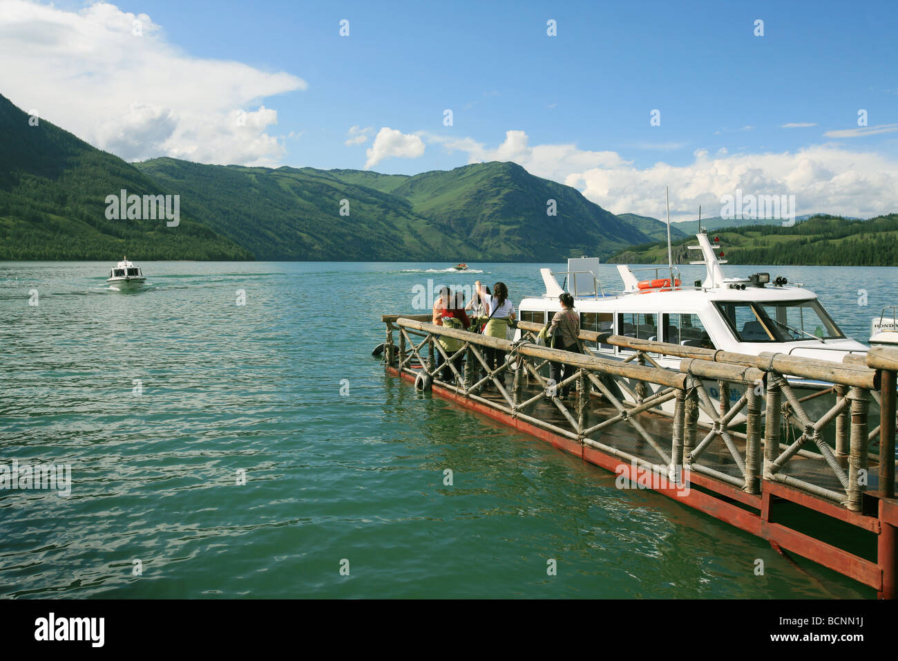 Tourists waiting to board tour boat on the pier, Kanas Lake, Xinjiang Uyghur Autonomous Region, China - Stock Image