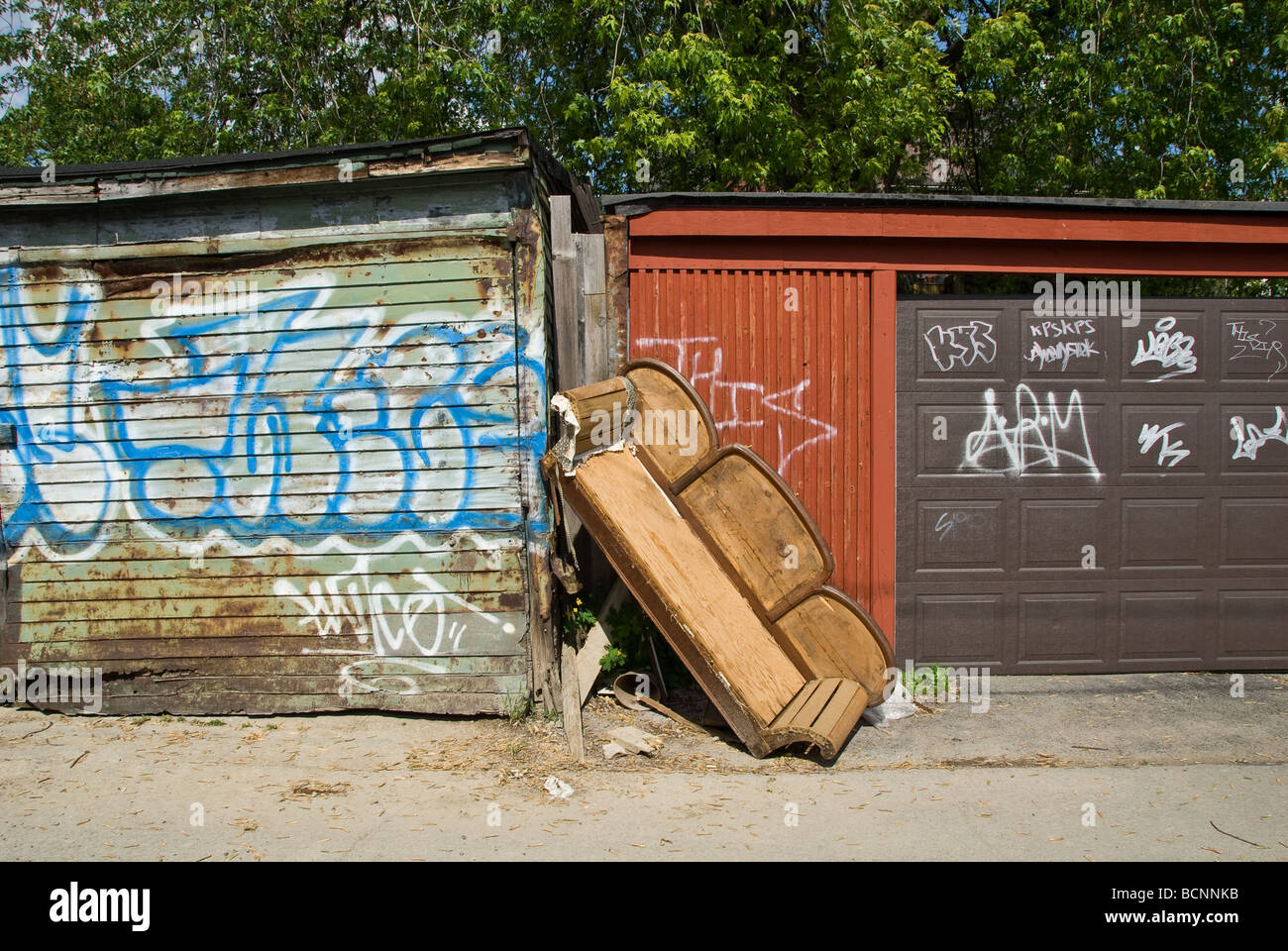Ruined sofa in grafitti-covered alleyway. - Stock Image