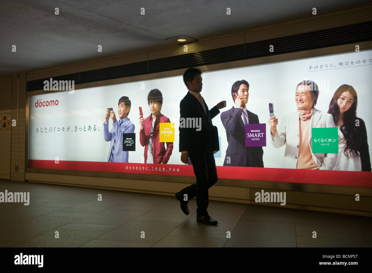 Pedestrian walk past billboard advertising DOCOMO the predominant mobile phone operator in Japan in an underground - Stock Image