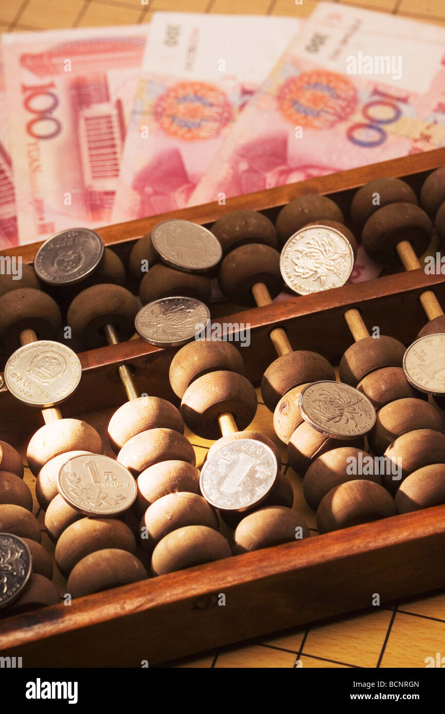 Chinese traditional calculator abacus with one hundred Chinese RMB bills and one Yuan coins - Stock Image