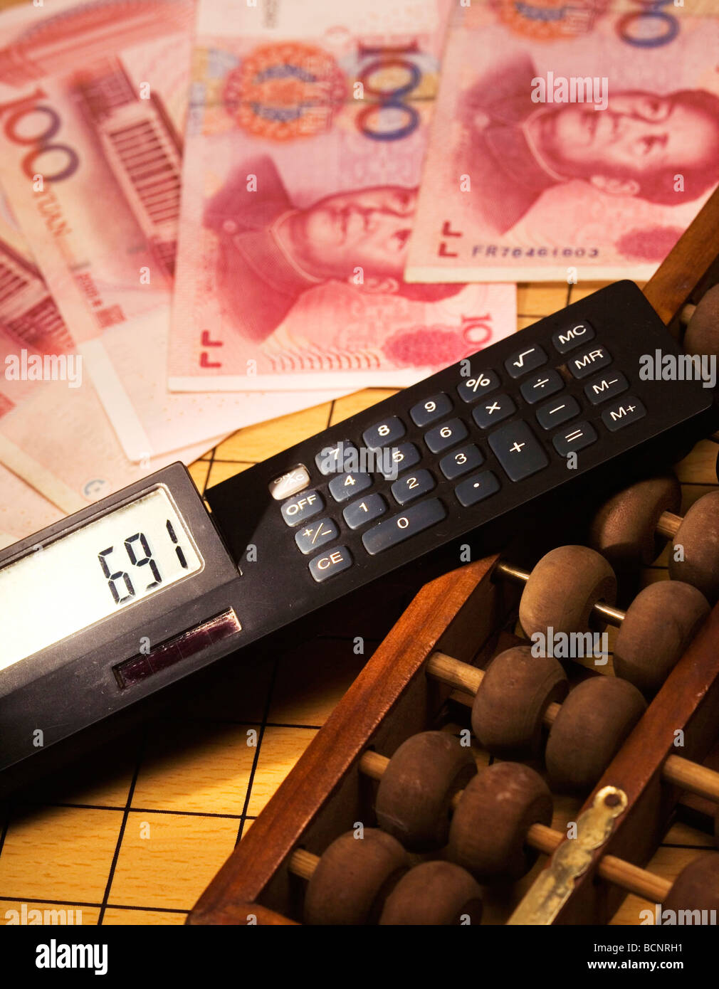 Chinese traditional calculator abacus and modern calculator with one hundred Chinese RMB bills - Stock Image