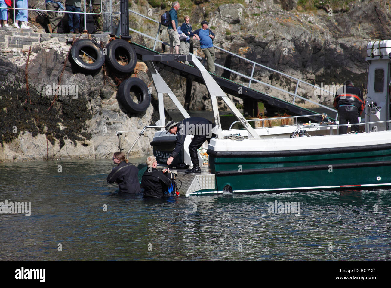 divers loading diving equipment onto boat in Cardigan bay West Wales - Stock Image