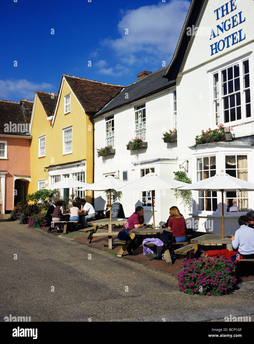 Visitors enjoying a drink outside the Angel Hotel in the old Suffolk village of Lavenham Stock Photo