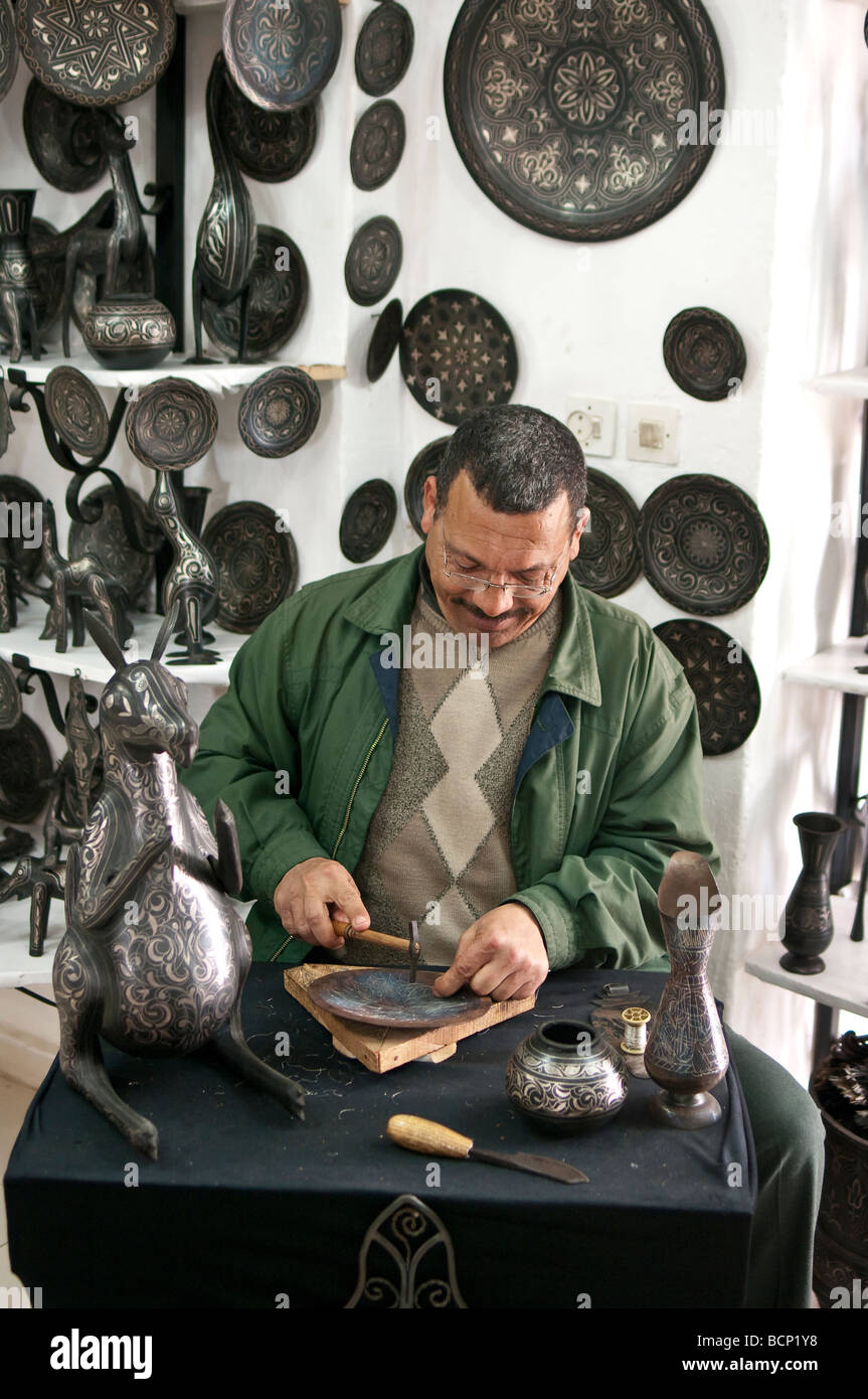 Arab craftsman decorating a plate with silver filigree in Meknes, Morocco Stock Photo