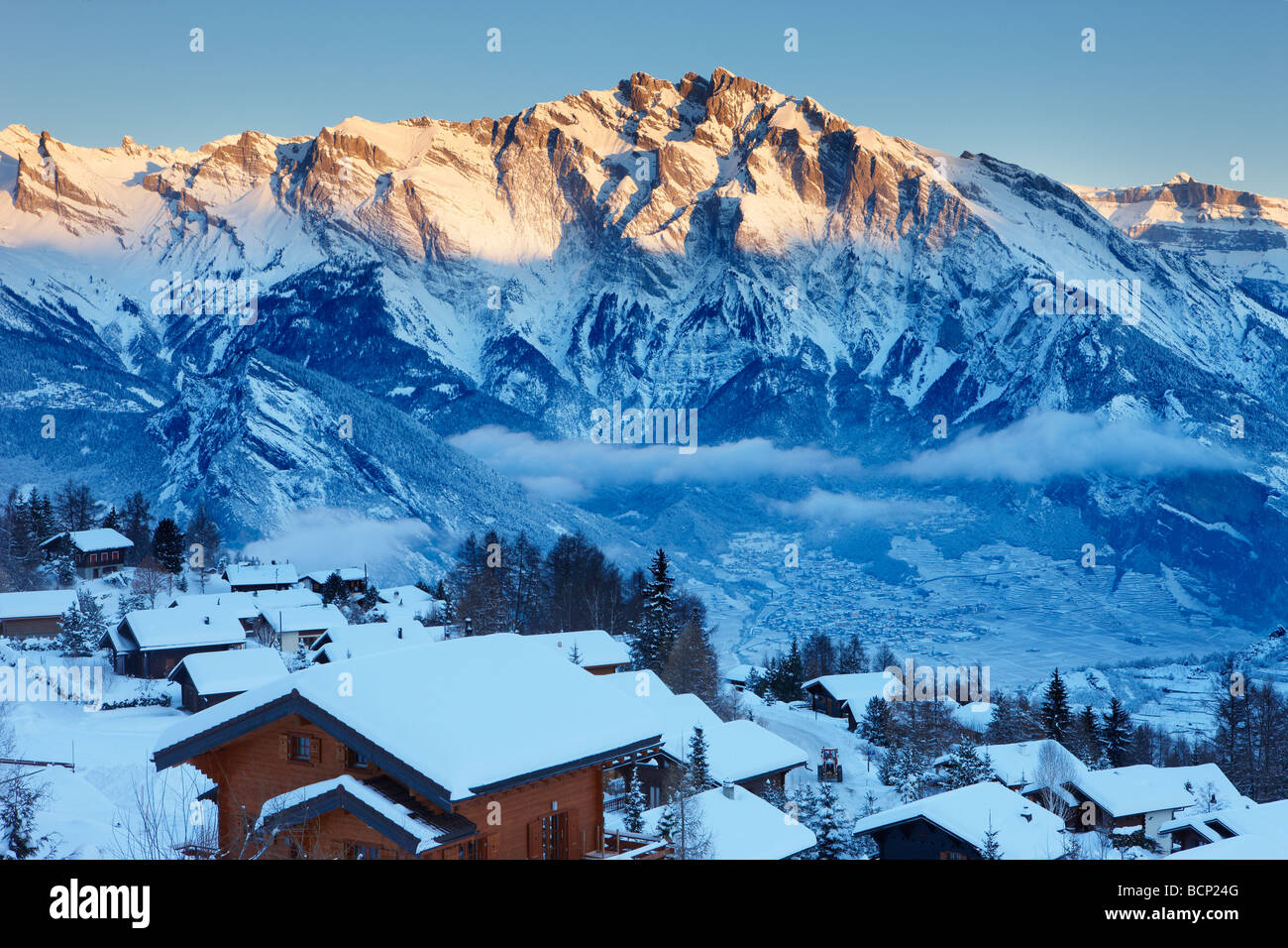 a fresh snowfall on the alpine village of La Tzoumas at dawn, with Iserables and Rhone Valley beyond, Valais Region, - Stock Image