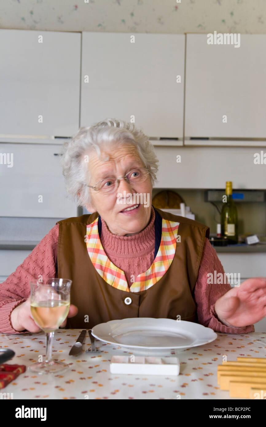 Frau in ihren Siebzigern sitzt in der Küche am gedeckten Mittagstisch - Stock Image