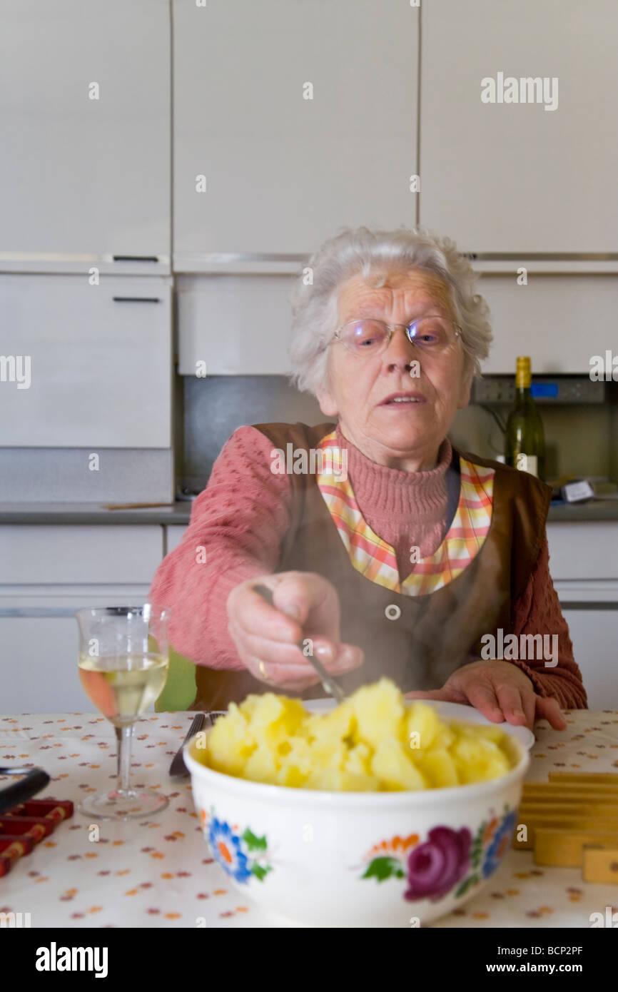 Frau in ihren Siebzigern sitzt in der Küche am gedeckten Mittagstisch und nimmt sich Kartoffeln auf ihren Teller - Stock Image