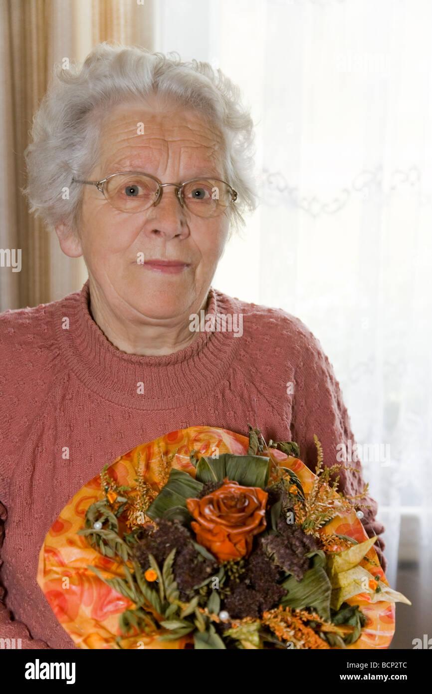 Frau in ihren Siebzigern steht im Wohnzimmer und hält einen künstlichen Blumenstrauß Stock Photo