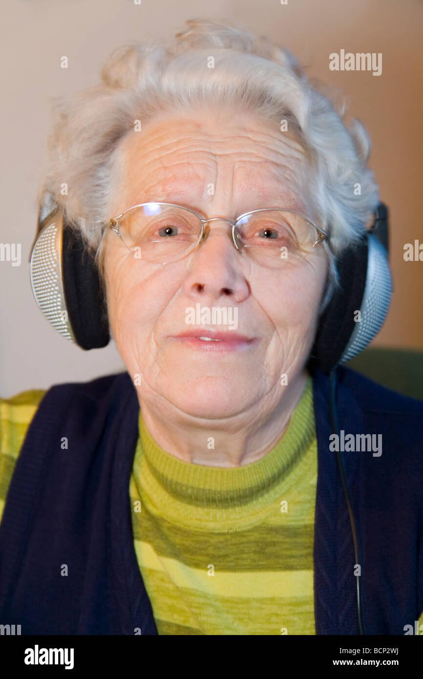 Frau in ihren Siebzigern hört Musik mit Kopfhörern - Stock Image