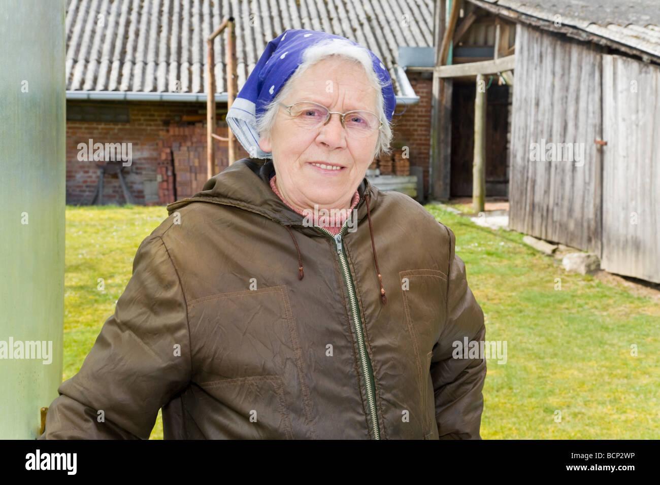 Frau in ihren Siebzigern mit Kopftuch posiert vor ihrem Bauernhof Stock Photo