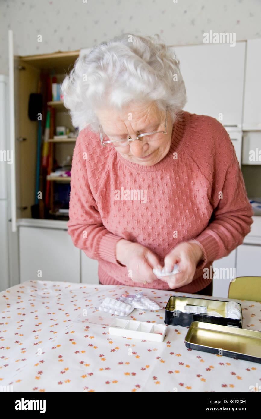 Frau in ihren Siebzigern steht am Küchentisch und sortiert ihre Tabletten in eine Pillendose - Stock Image