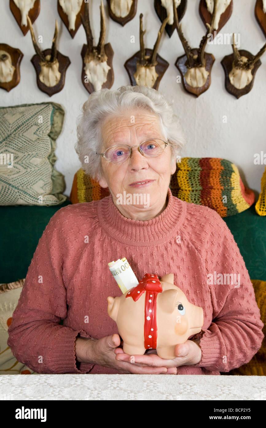 Frau in ihren Siebzigern sitzt auf einem Sofa im Wohnzimmer und hält ein Sparschwein mit Geldscheinen im Schlitz - Stock Image