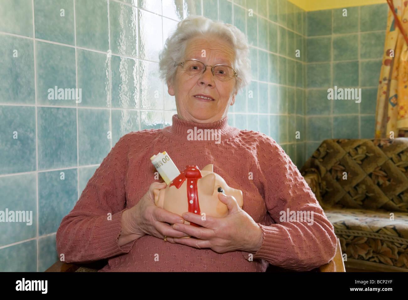 Frau in ihren Siebzigern sitzt auf einem Sessel und hält ein Sparschwein mit Geldscheinen - Stock Image