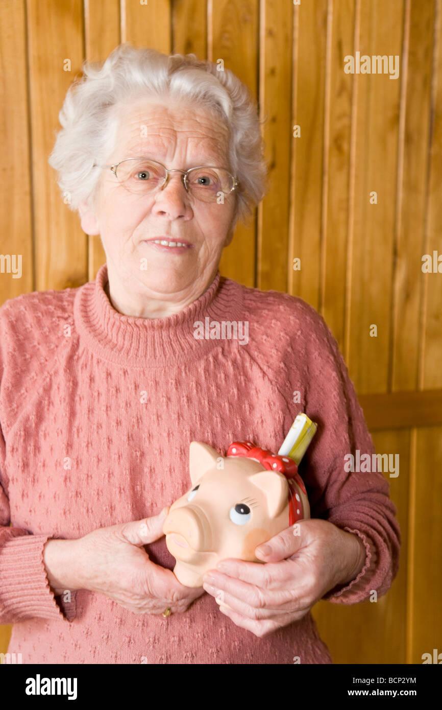 Frau in ihren Siebzigern steht vor einer Holzvertäfelung und hält lachend ein Sparschwein in den Händen - Stock Image