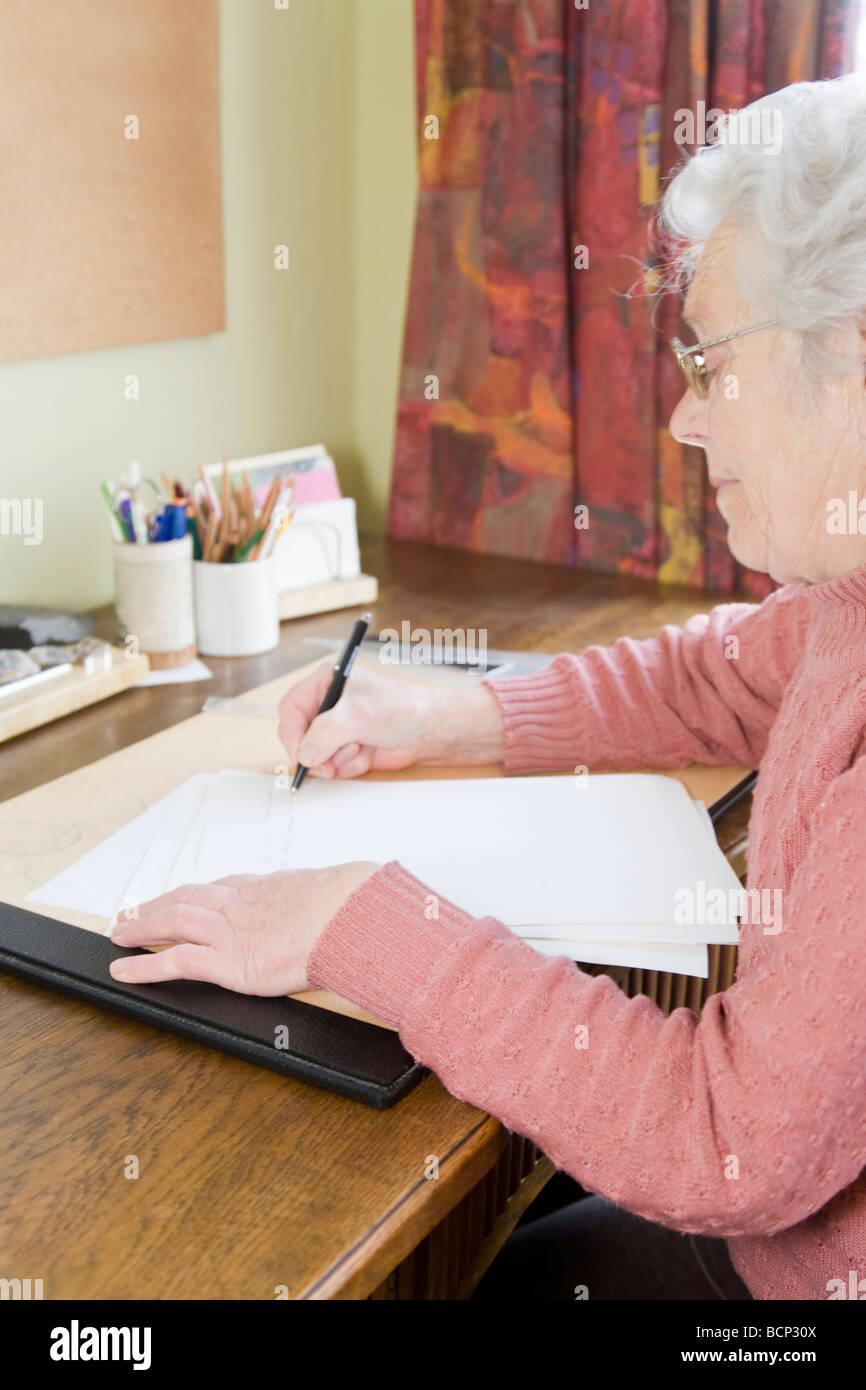 Frau in ihren Siebzigern sitzt am Schreibtisch und schreibt einen Brief Stock Photo