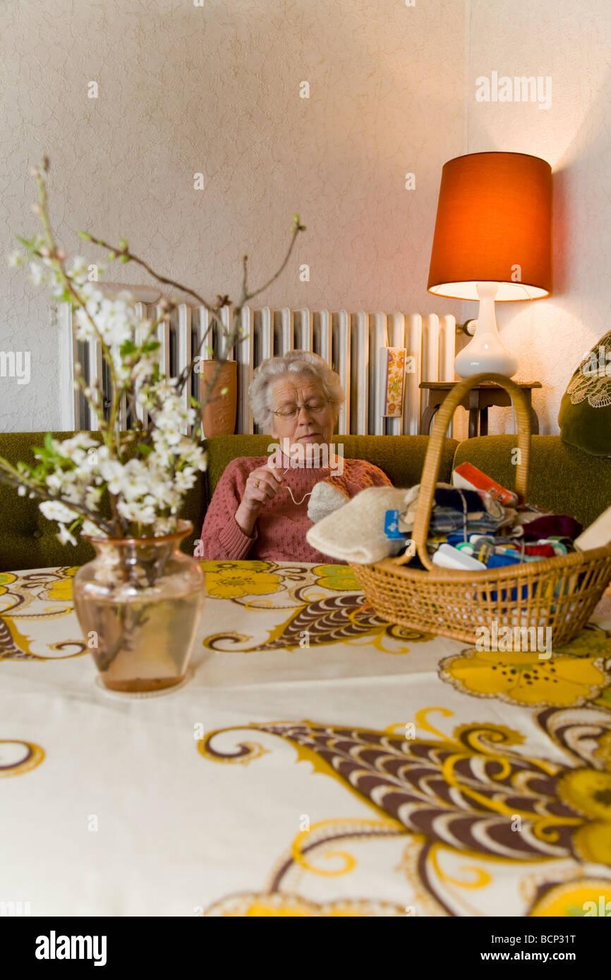 Frau in ihren Siebzigern sitzt im Wohnzimmer und stopft Wollsocken ...