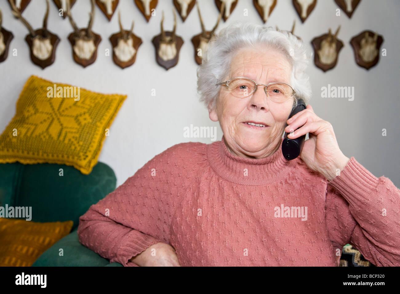 Frau in ihren Siebzigern sitzt in einem Sessel im Wohnzimmer und ...