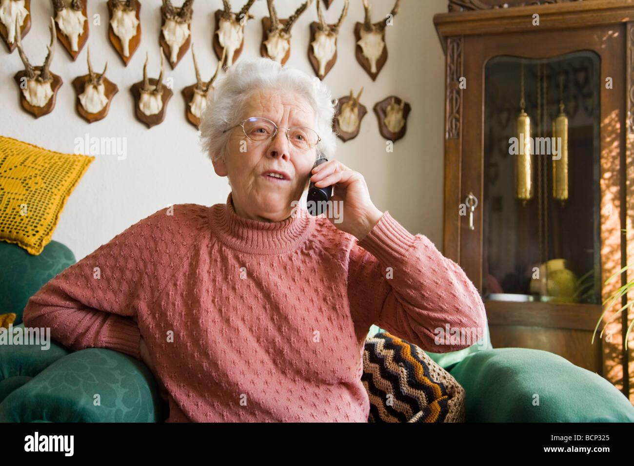 Frau in ihren Siebzigern sitzt in einem Sessel im Wohnzimmer und telefoniert mit einem schnurlosen Telefon Stock Photo