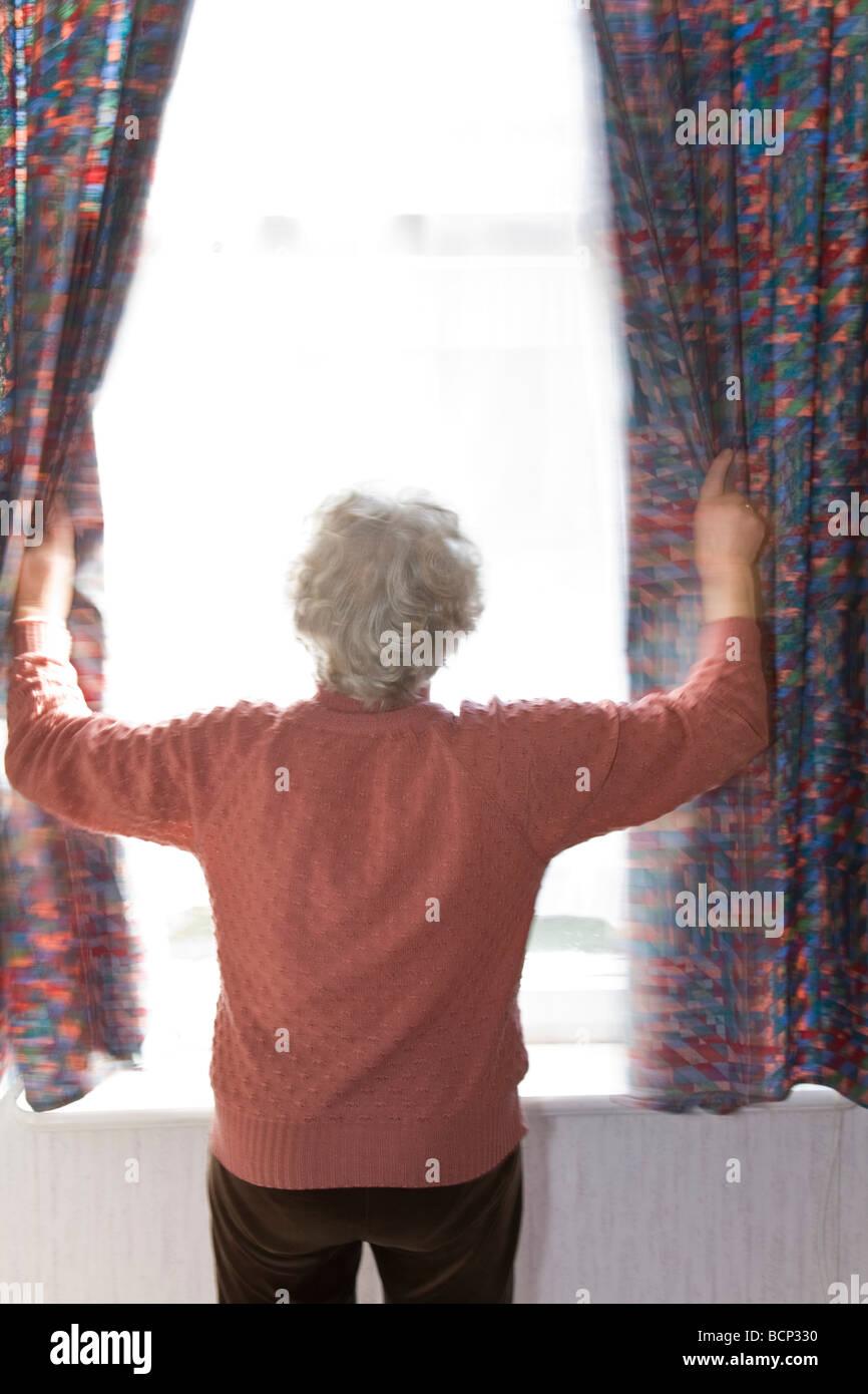 Frau in ihren Siebzigern steht morgens am Fenster und zieht die Gardinen zur Seite - Stock Image