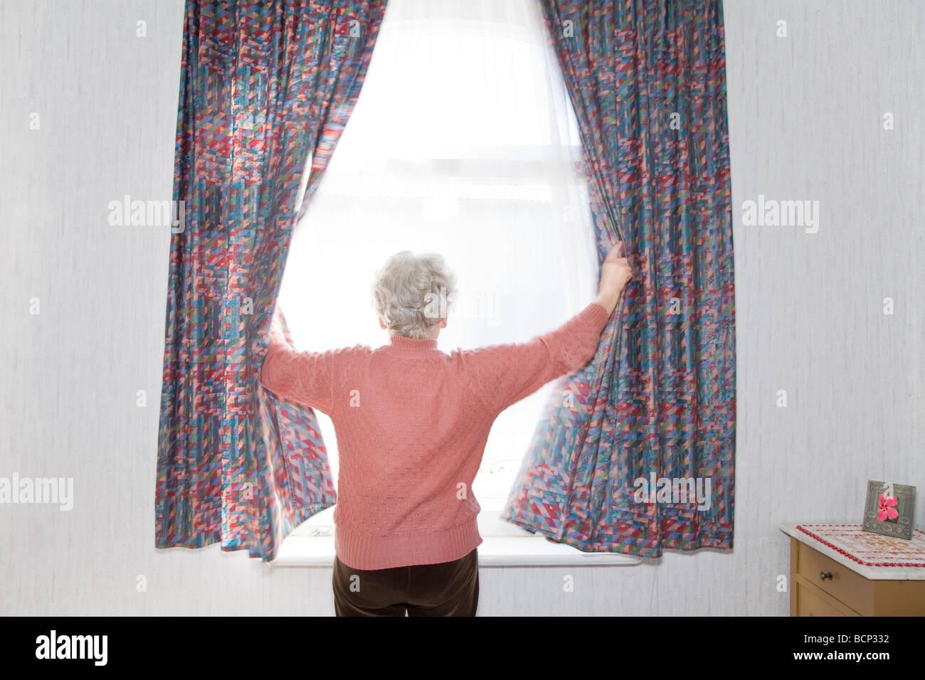 Frau in ihren Siebzigern steht morgens am Fenster und zieht die Vorhänge zur Seite - Stock Image