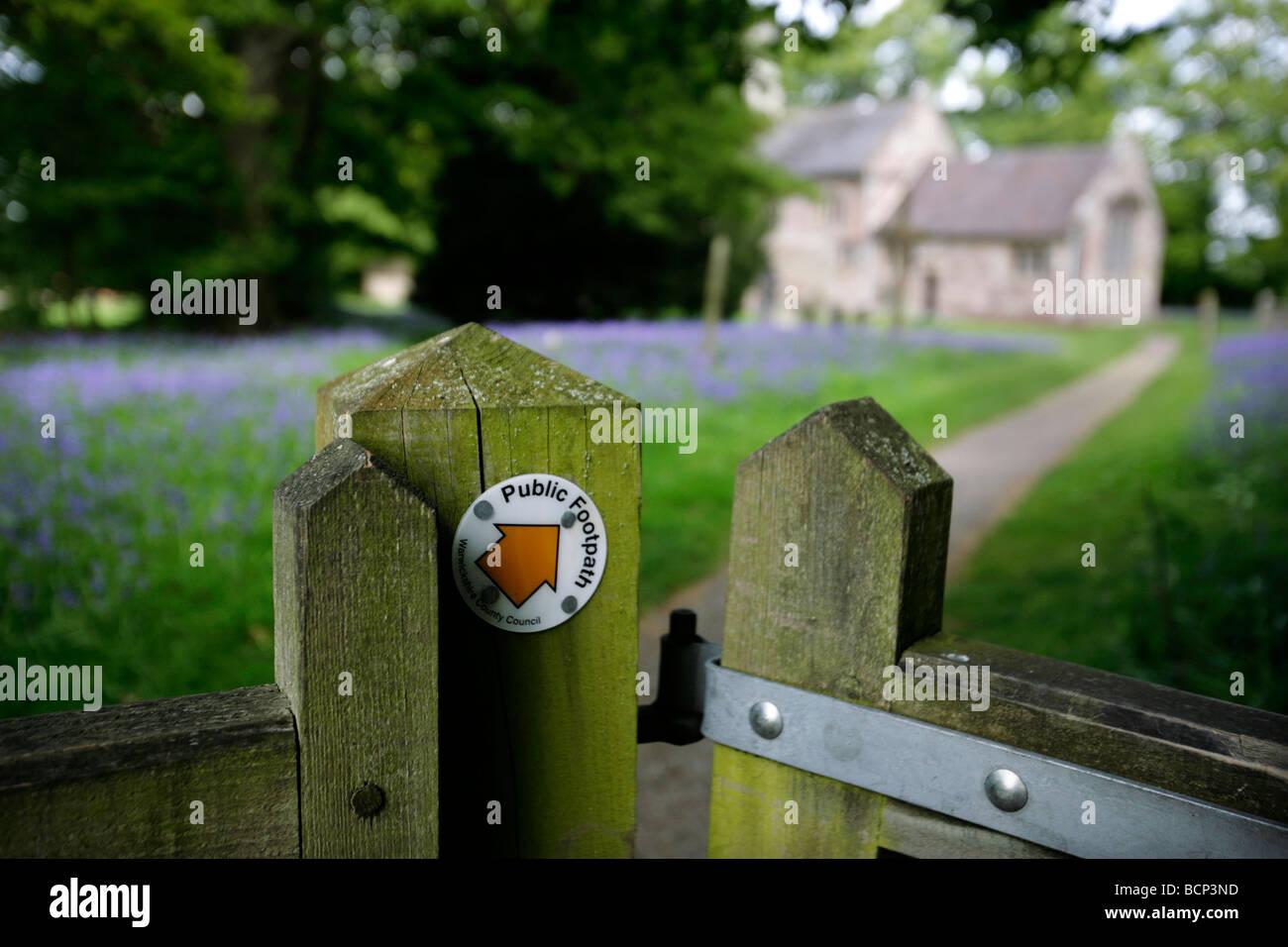A public footpath leading through a churchyard in Warwickshire, UK - Stock Image