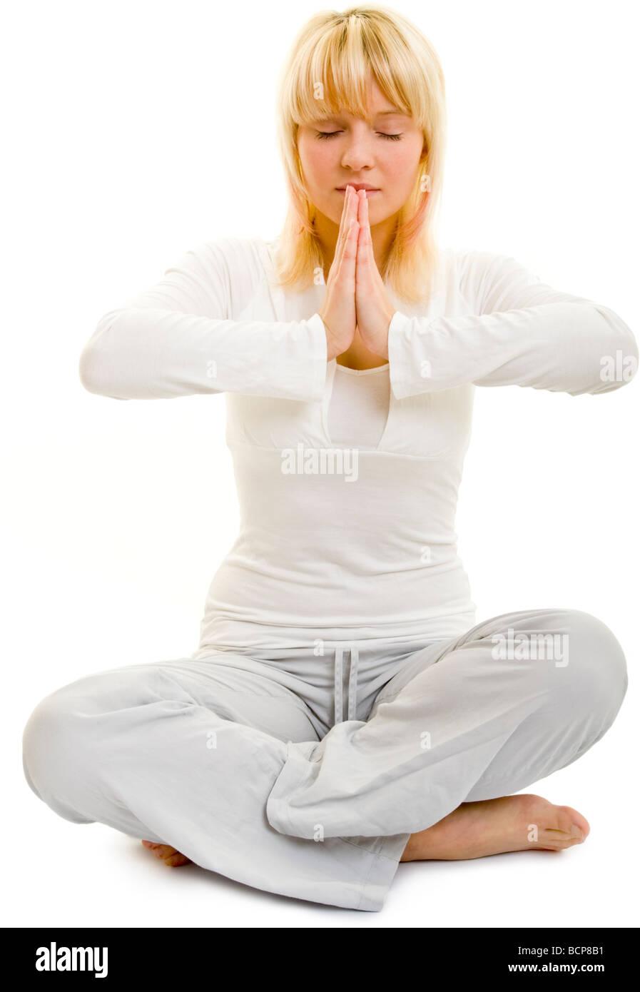 Junge blonde Frau in weißer Kleidung mit geschlossenen Augen faltet die Hände zusammen - Stock Image