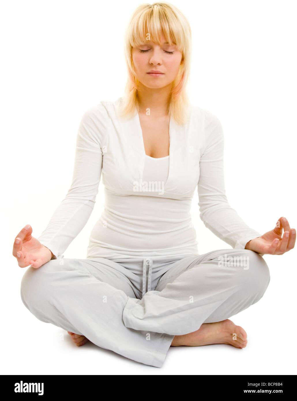 Junge Frau meditiert im Schneidersitz mit geschlossenen Augen - Stock Image