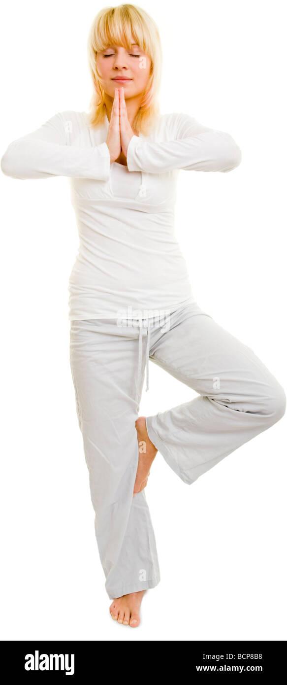 Junge Frau steht auf einem Bein mit geschlossenen Augen und meditiert Stock Photo
