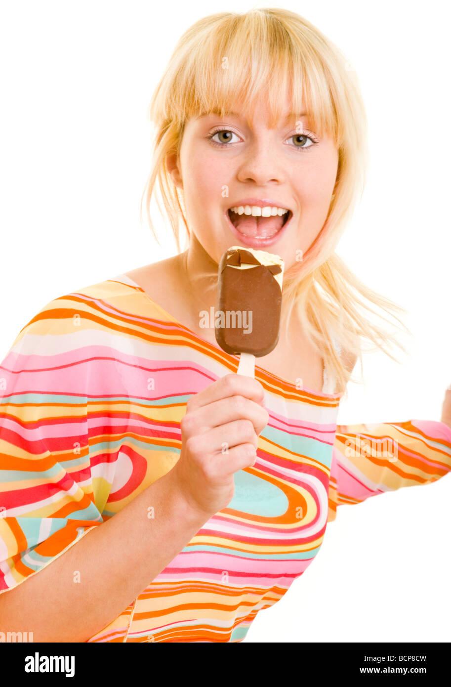 Junge blonde Frau tanzt im Sommerkleid und isst dabei ein Stieleis - Stock Image