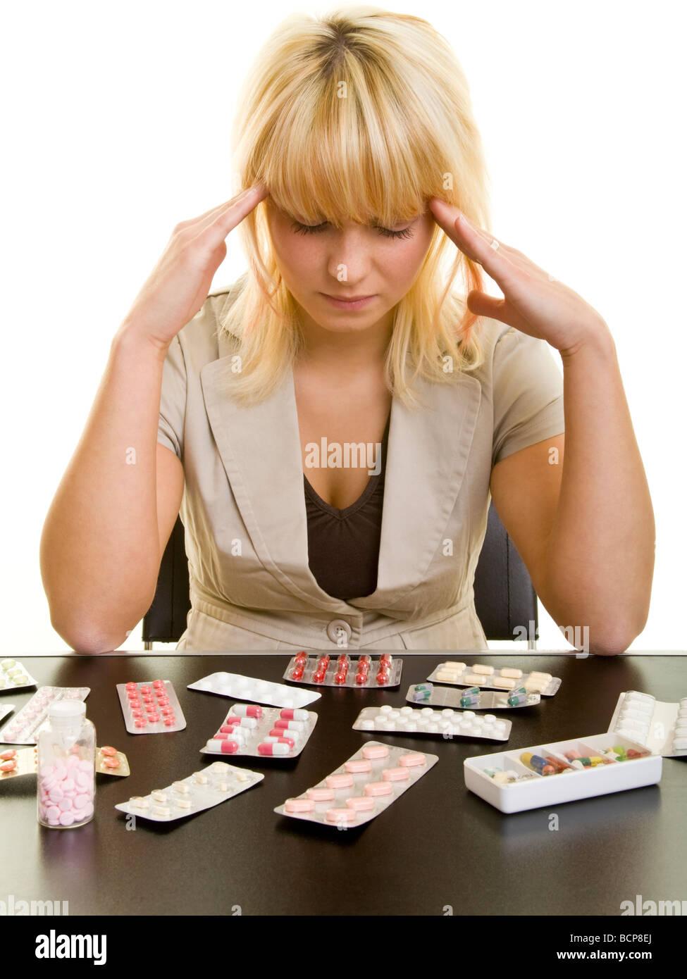 Junge Frau sitzt mit Kopfschmerzen vor einem Tisch mit vielen Arzneimitteln Stock Photo
