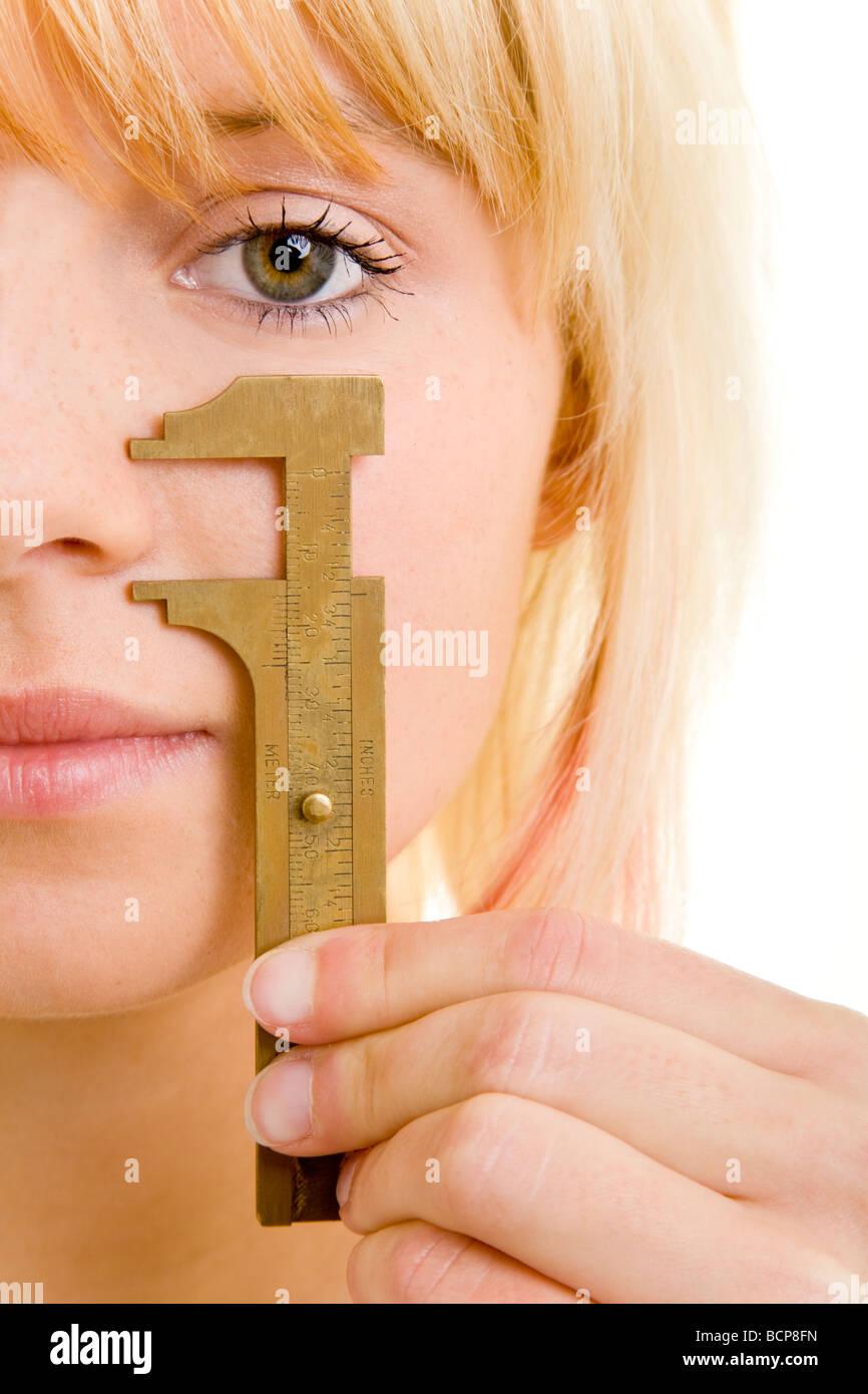 Junge blonde Frau hält sich eine Schublehre an ihre Nase Stock Photo