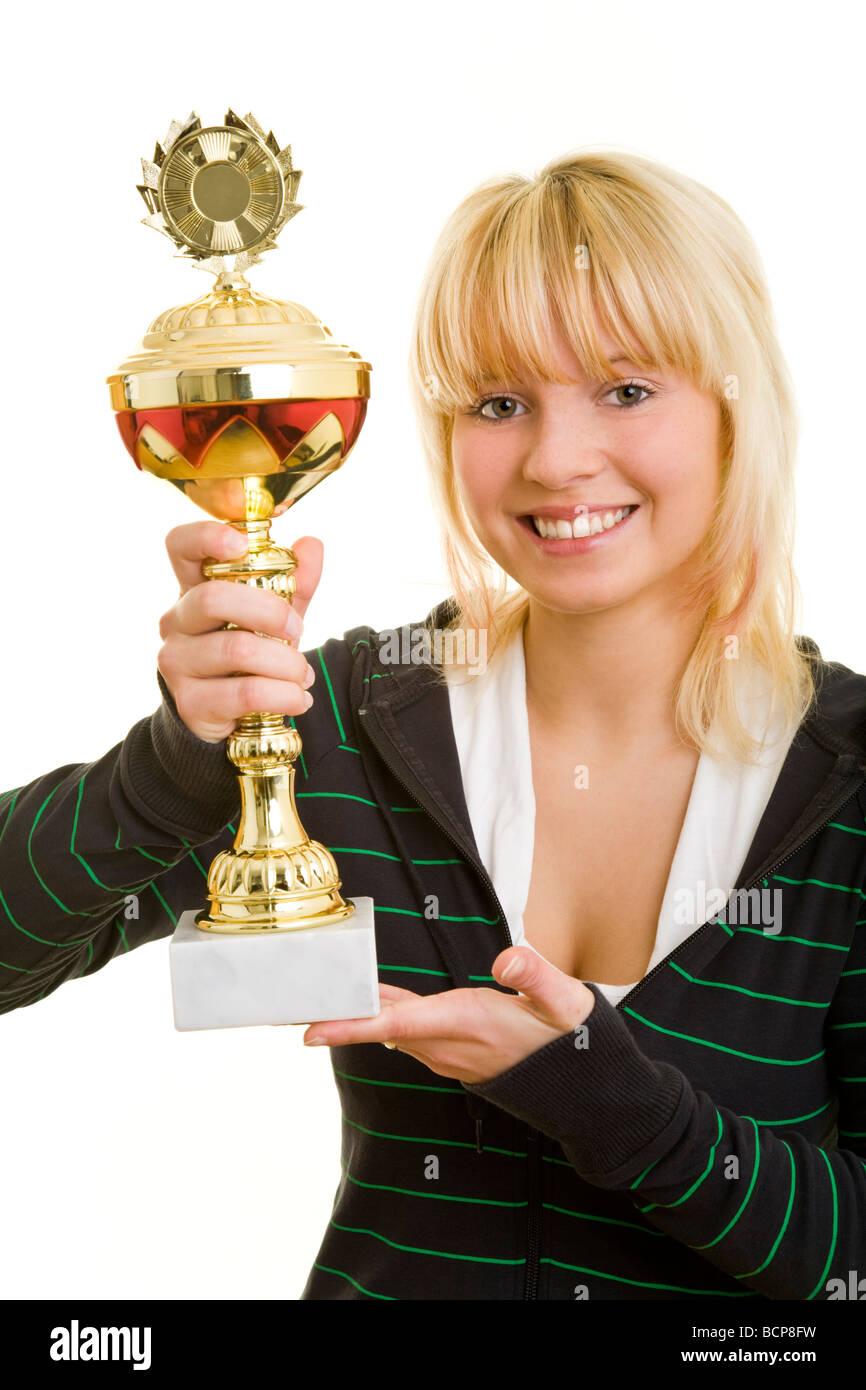 Junge Frau in Sportkleidung hält lachend einen Pokal Stock Photo
