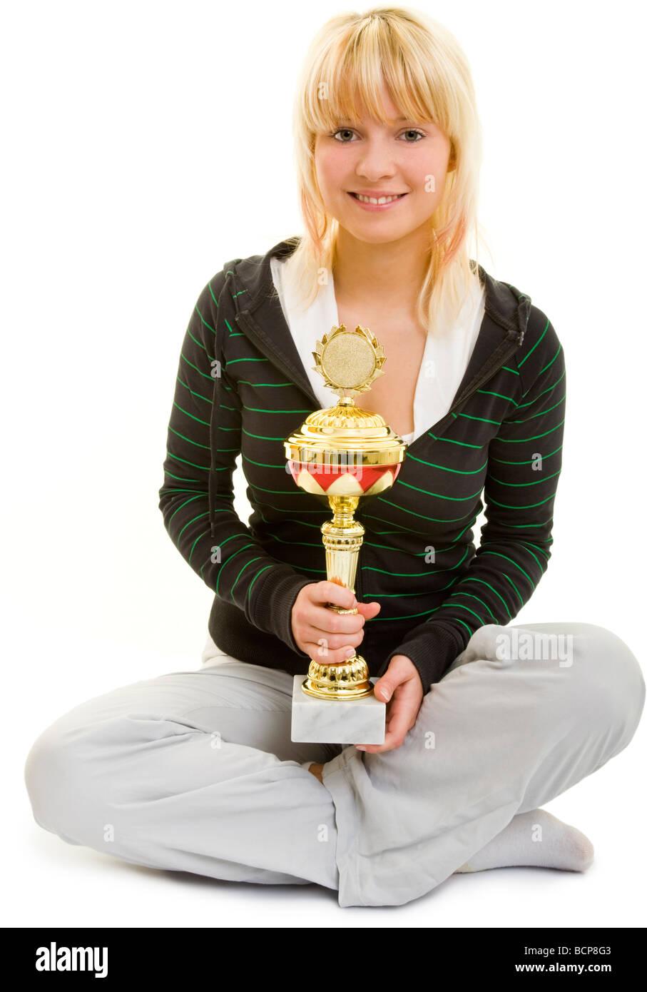 Junge Frau in Sportkleidung sitzt im Schneidersitz und hält lachend einen Pokal - Stock Image