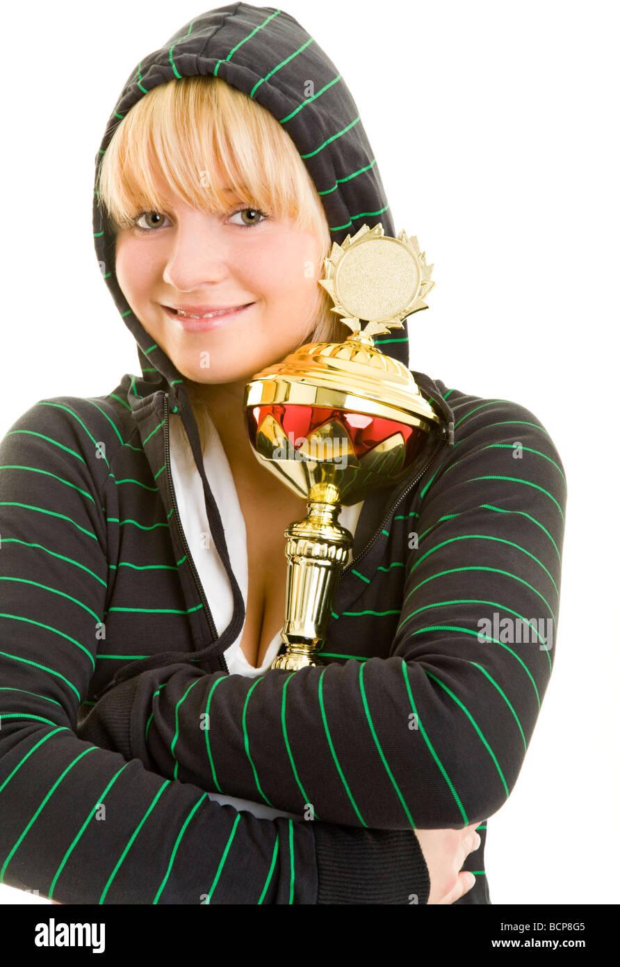 Junge Frau in Sportkleidung umarmt lachend einen Pokal Stock Photo