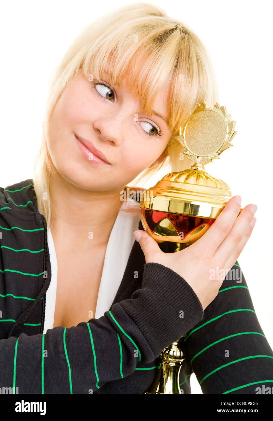 Junge Frau in Sportkleidung umarmt einen Pokal - Stock Image