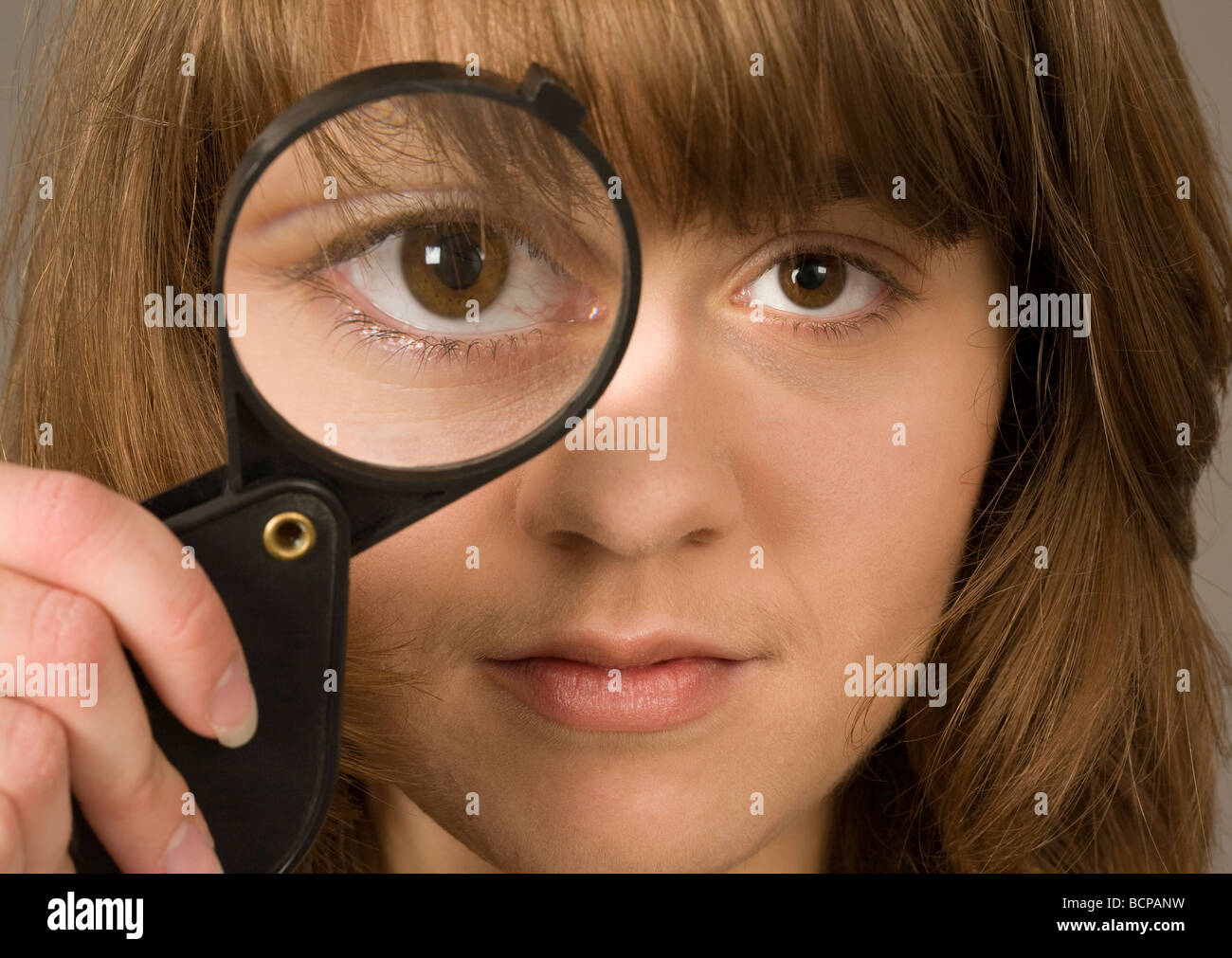 A young woman in her twenties looking through a magnifying glass - Stock Image
