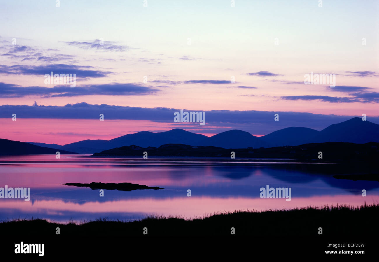 The island of Taransay with the south Harris hills at sunset - Stock Image