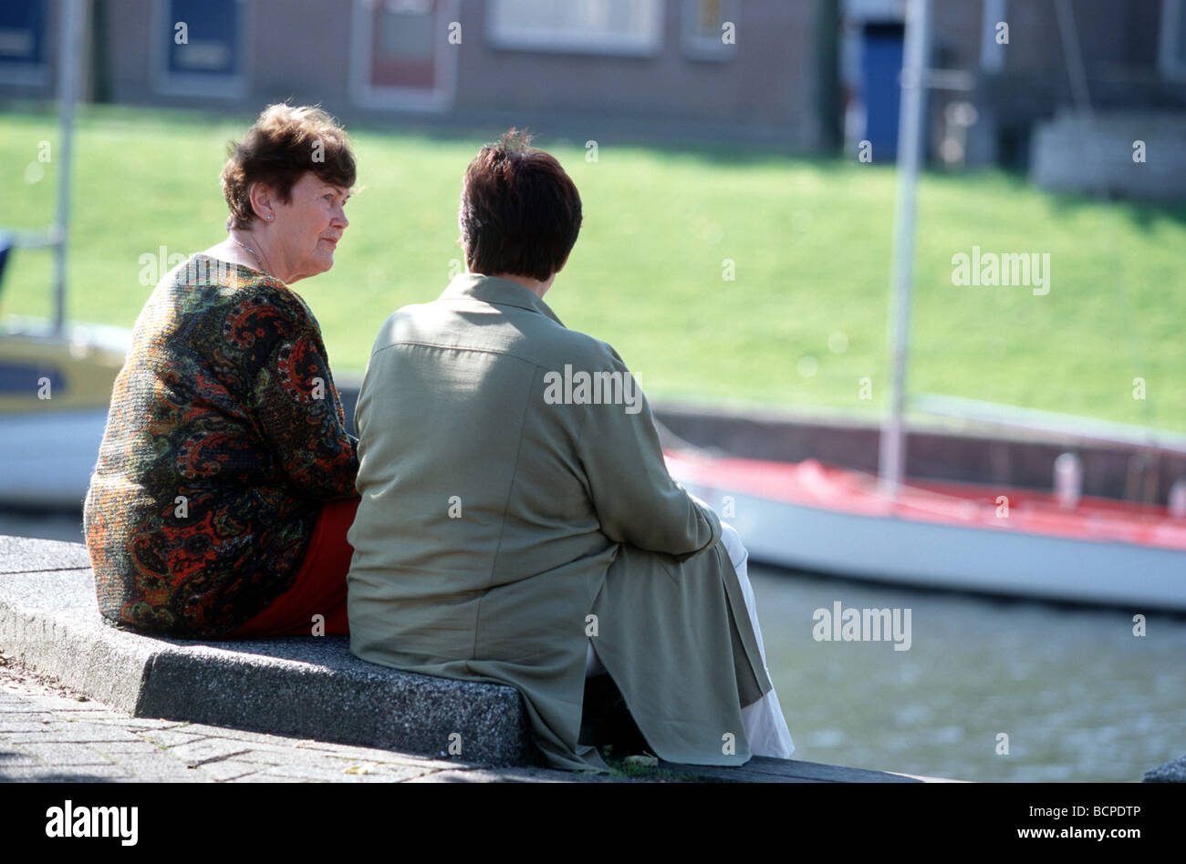 Two women telling the truth or spreading lies or secrets, rear view - Stock Image