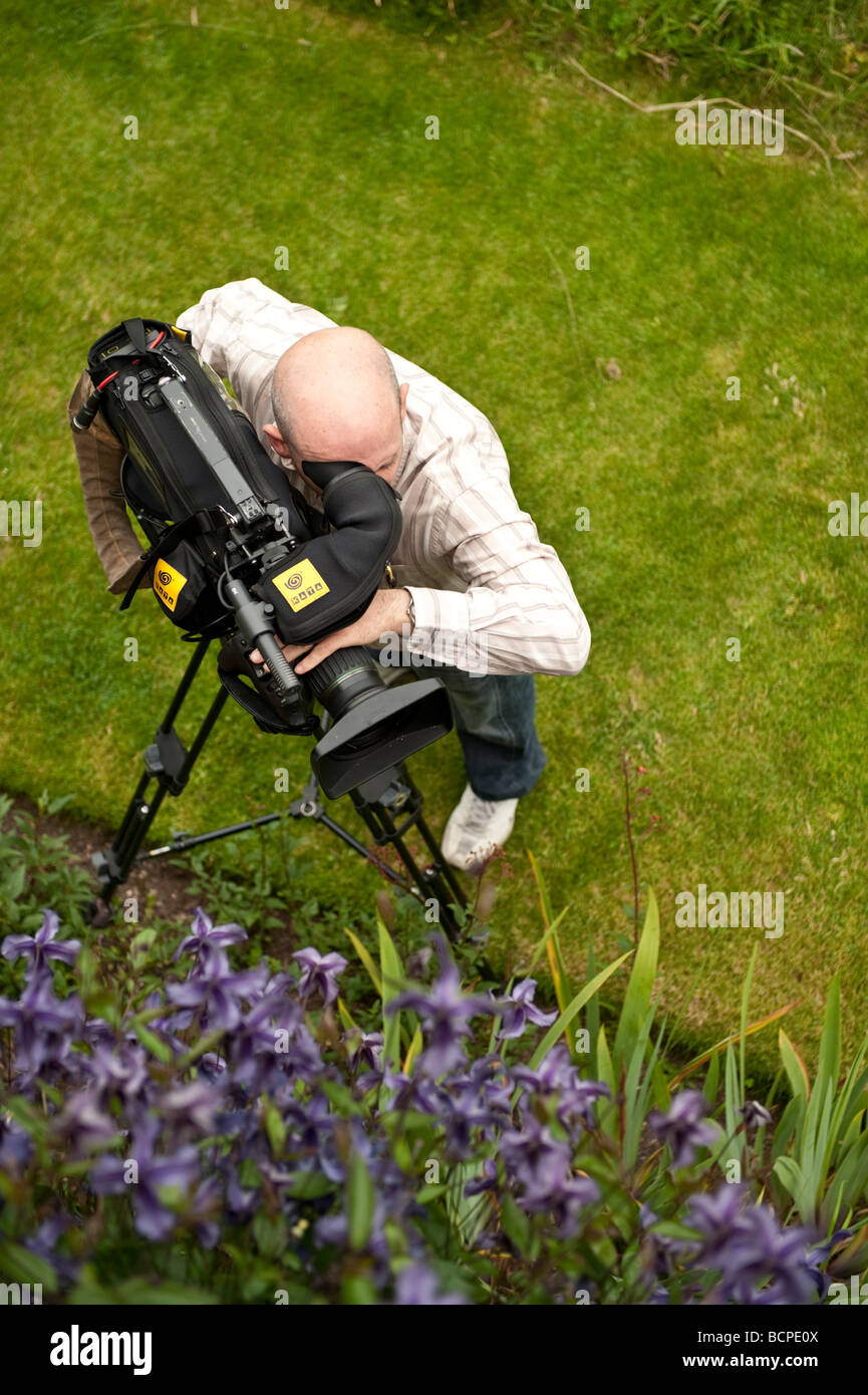 A freelance self employed Cameraman filming the plants and flowers at Powis Castle welshpool Powys WALES UK - Stock Image