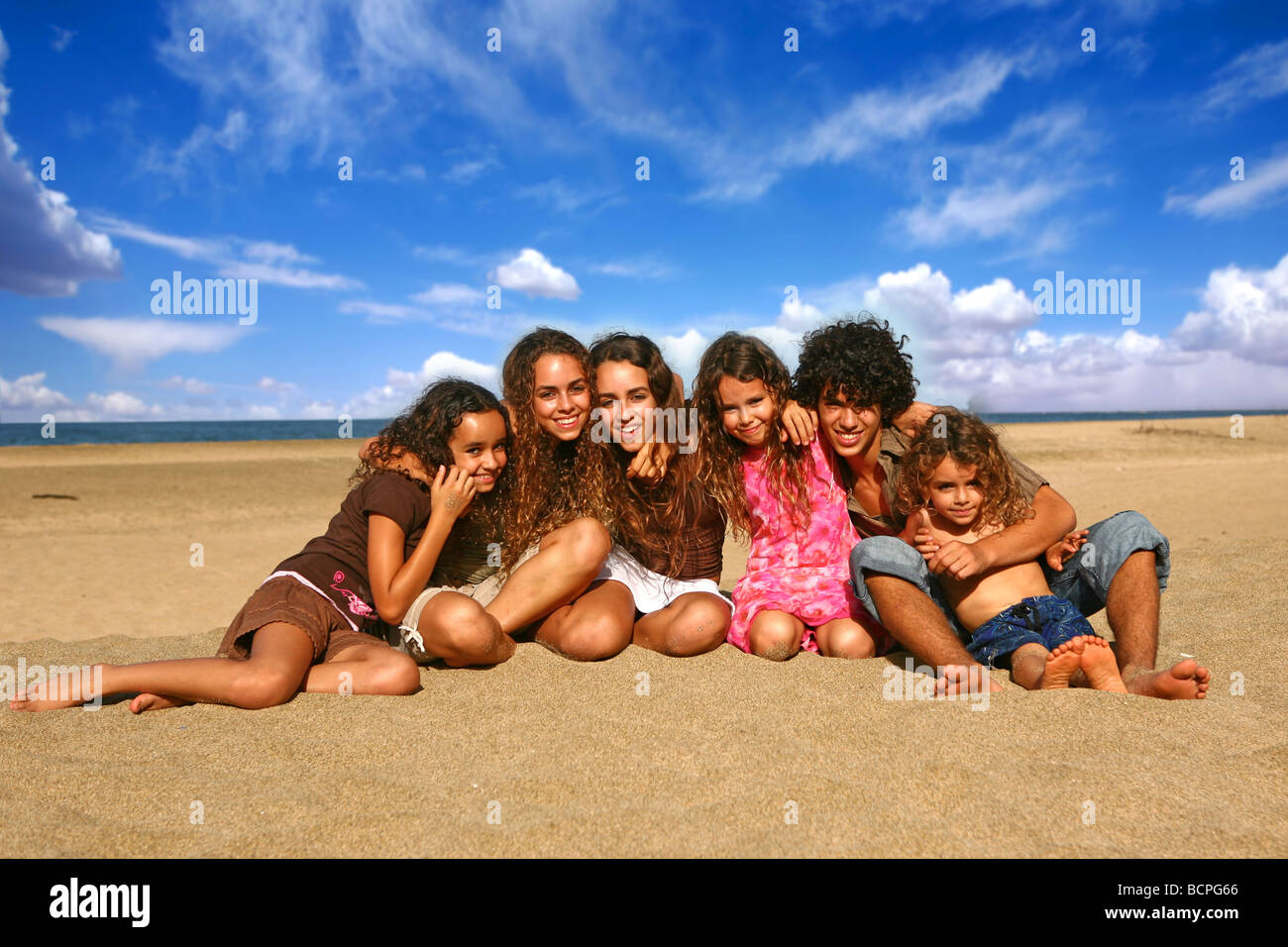 Family of 6 Happy Kids Smiling Outdoors at the Beach - Stock Image