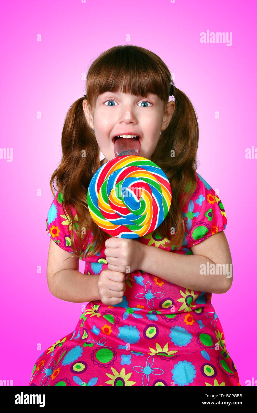 Portrait of a Funny Little Girl Licking a Lollipop - Stock Image