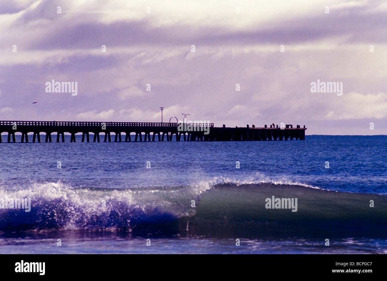 Tolaga Bay with wharf with small wave breaking on the beach in the foreground East Coast New Zealand - Stock Image