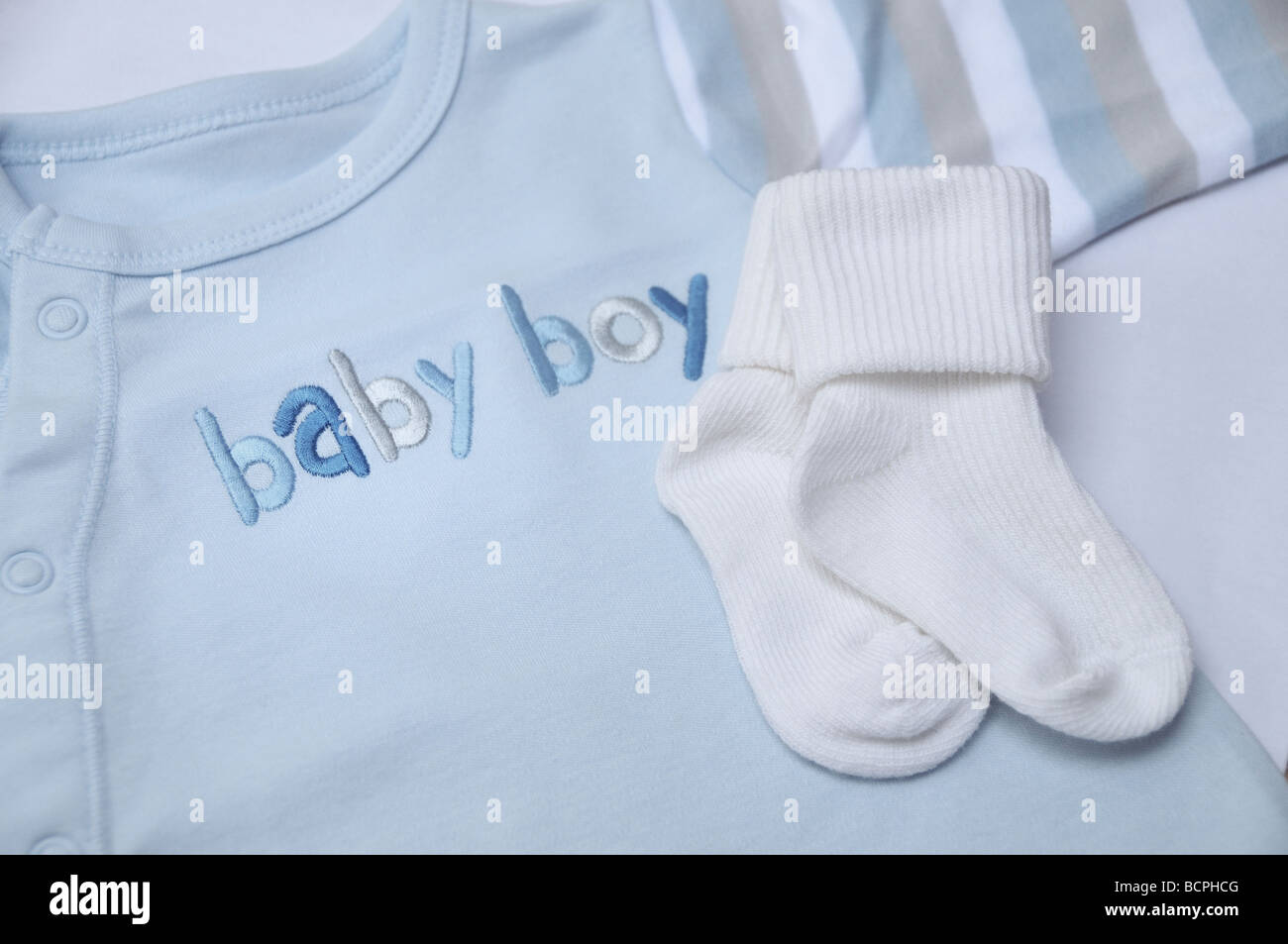 Baby boy clothes detail (folded blue bodysuit and tiny white socks ...