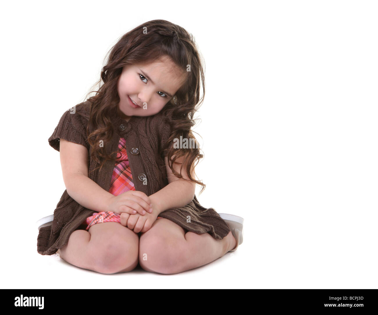 Cute Brown Haired Young Girl Tilting Her Head Sideways - Stock Image