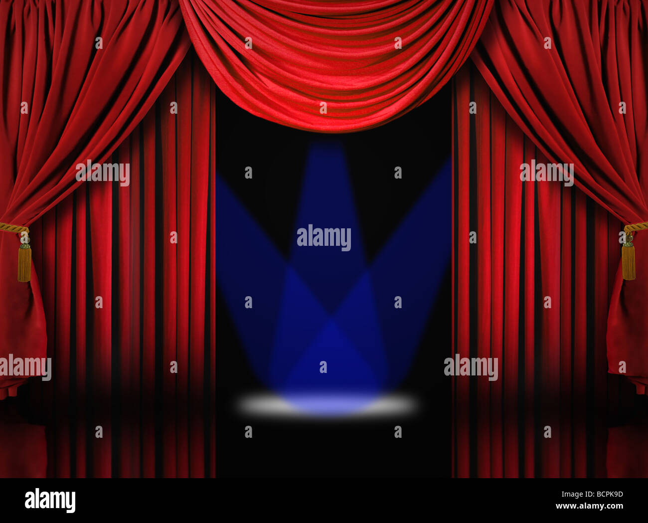 Beautiful Red Velvet Theater Stage Drape Curtains With Blue Spotlights - Stock Image