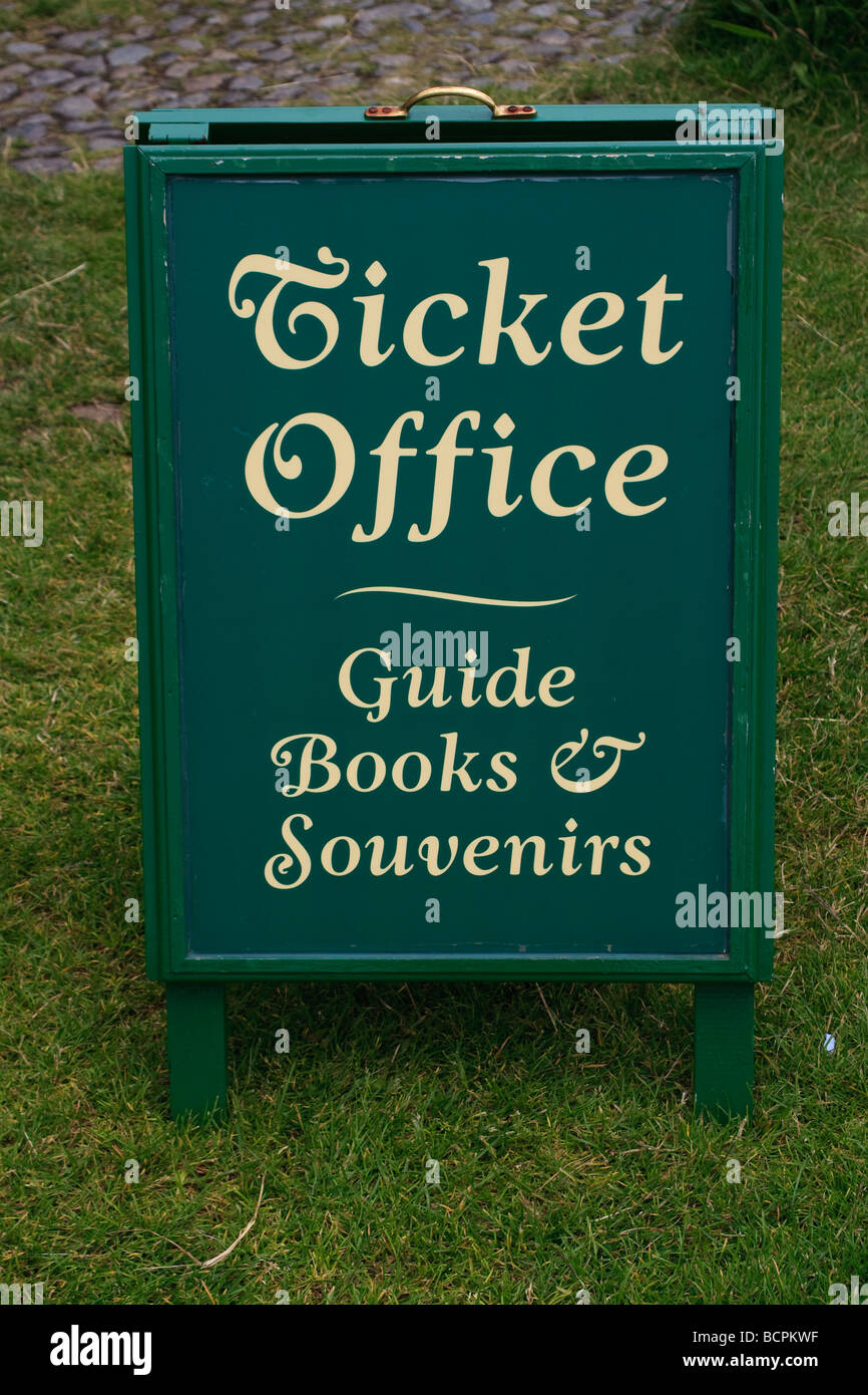 A wooden sign indicating a ticket office with guide books and souvenirs - Stock Image